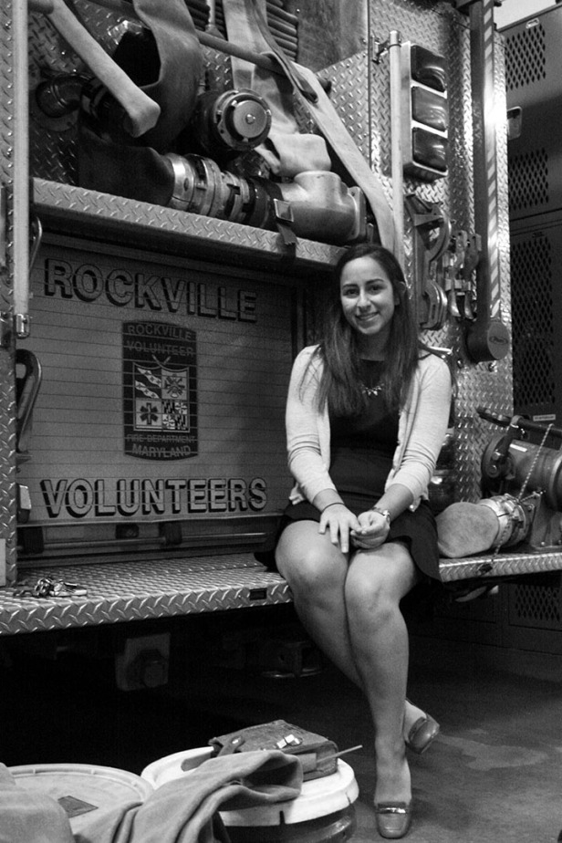 After commuting for two hours in traffic from her job in downtown Washington, D.C., Saba Tabriz, 22, sits on the back of a rescue engine in her office attire before changing into proper firefighting gear for her night shift.