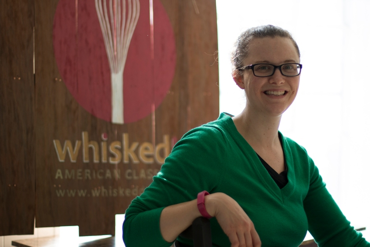 Huntsberger poses for a photo in the kitchen's office on Mt. Olivet Rd. in front of the Whisked! logo.
